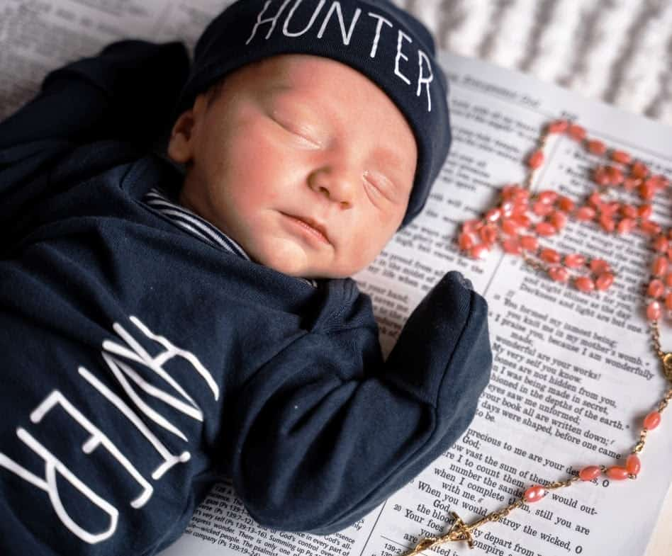 Photo of a baby boy with a Bible and a prayer rosary beside him