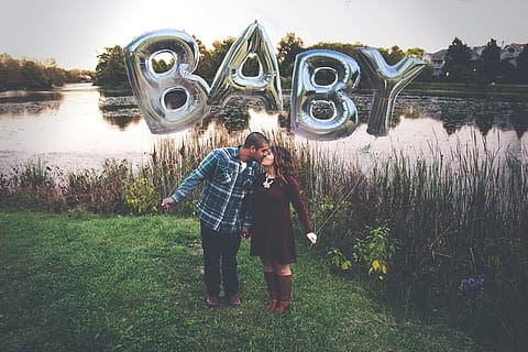 Photo of a couple with a balloon announcing the pregnancy