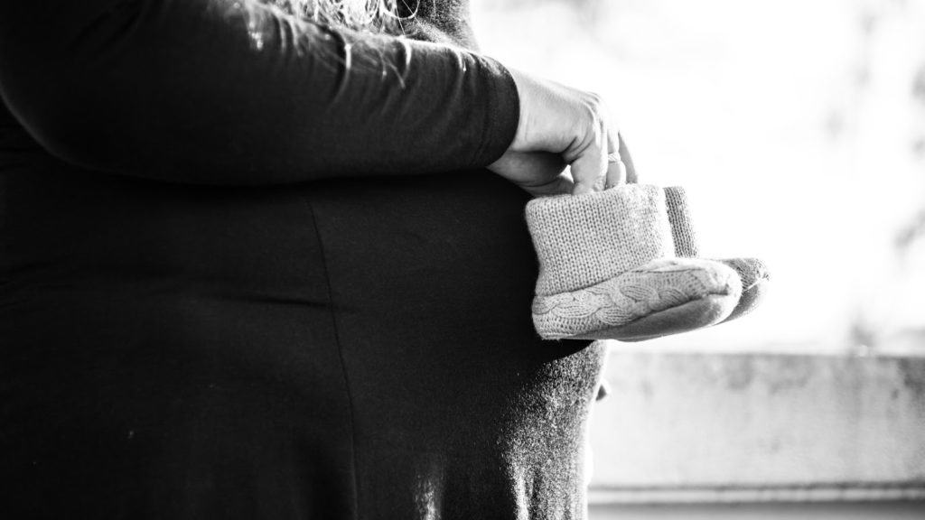 Photo of a woman holding baby shoes to her stomach; a maternity photoshoot Idea