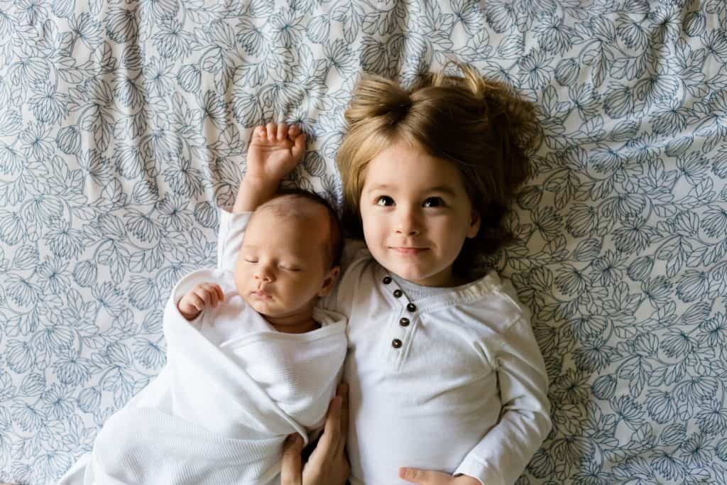 Photo of two lovely children lying on a pretty crib sheet