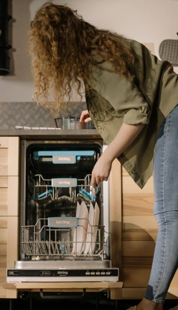 Photo of a woman loading a dish washer