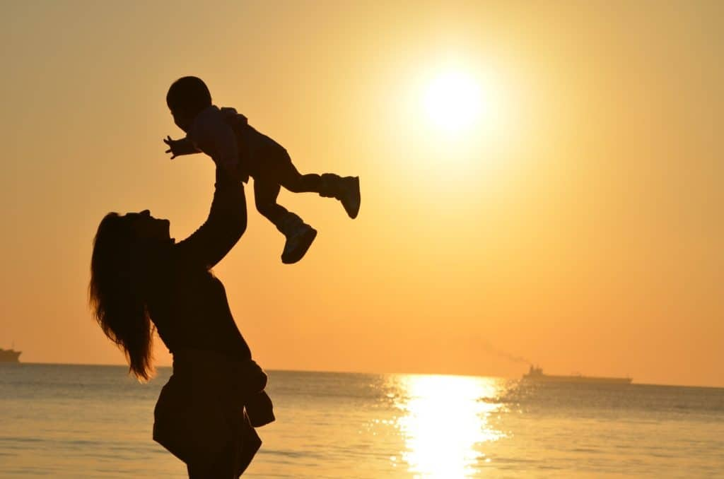 Photo of a mother lifting her son in the air with the sunset in the background
