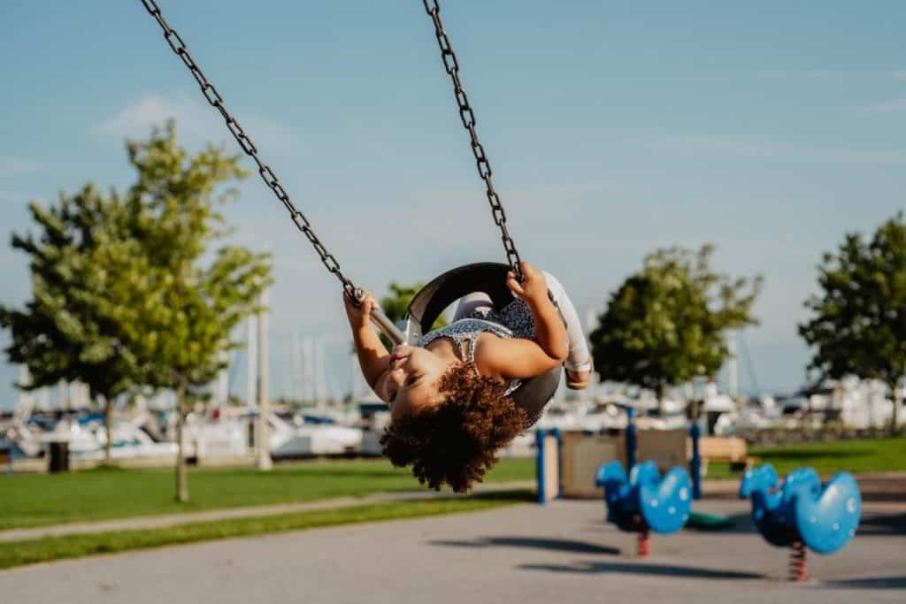 A toddler on an outdoor baby swing