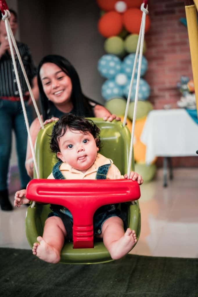 A baby being pushed on an outdoor baby swing