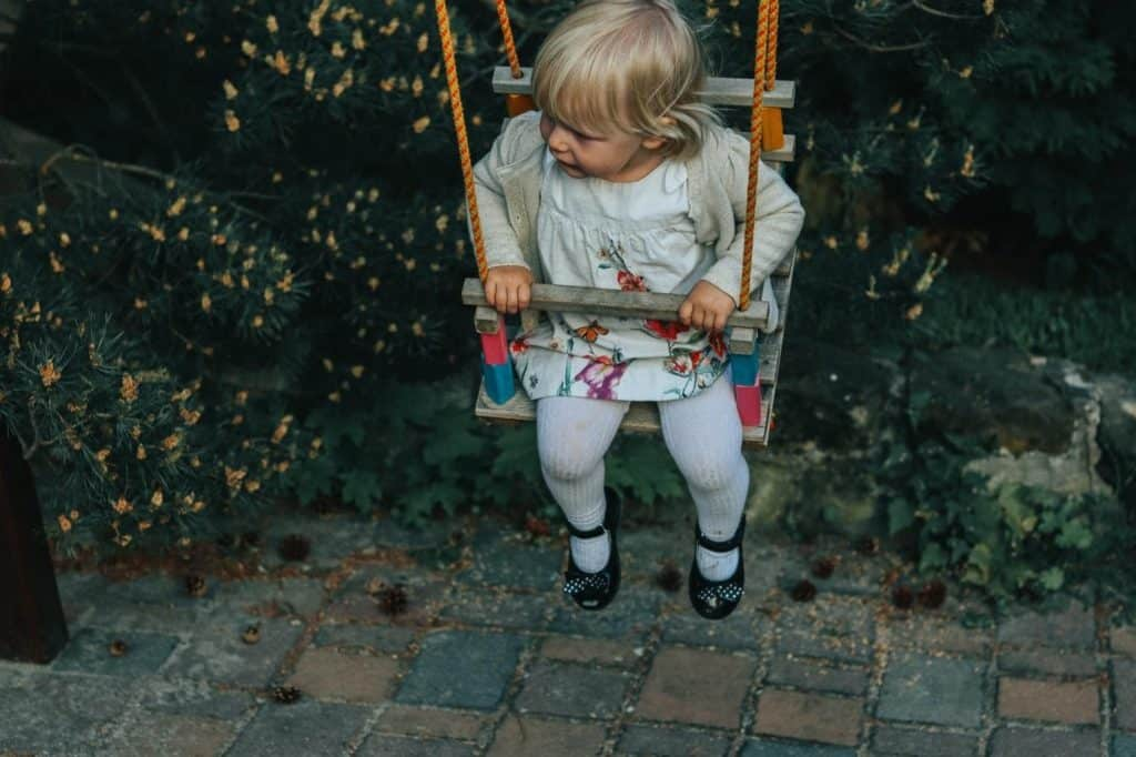 Photo of a baby on an outdoor baby swing