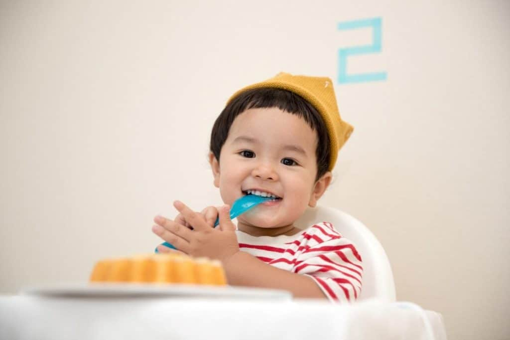 Photo of a baby eating; organic baby food is best for your baby