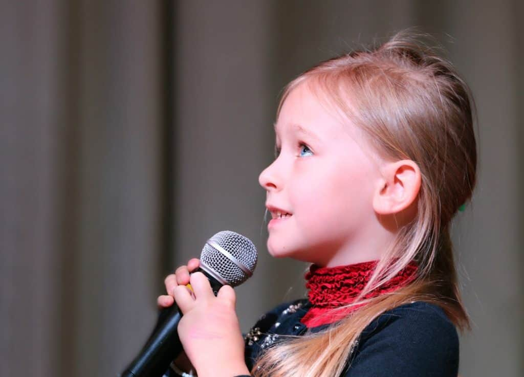 Photo of a girl singing; French children's songs are fun and catchy