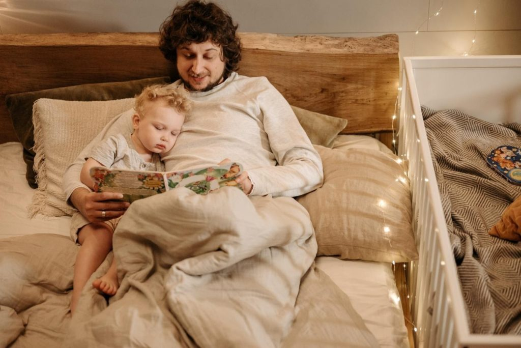 Photo of a dad co-sleeping with newborn